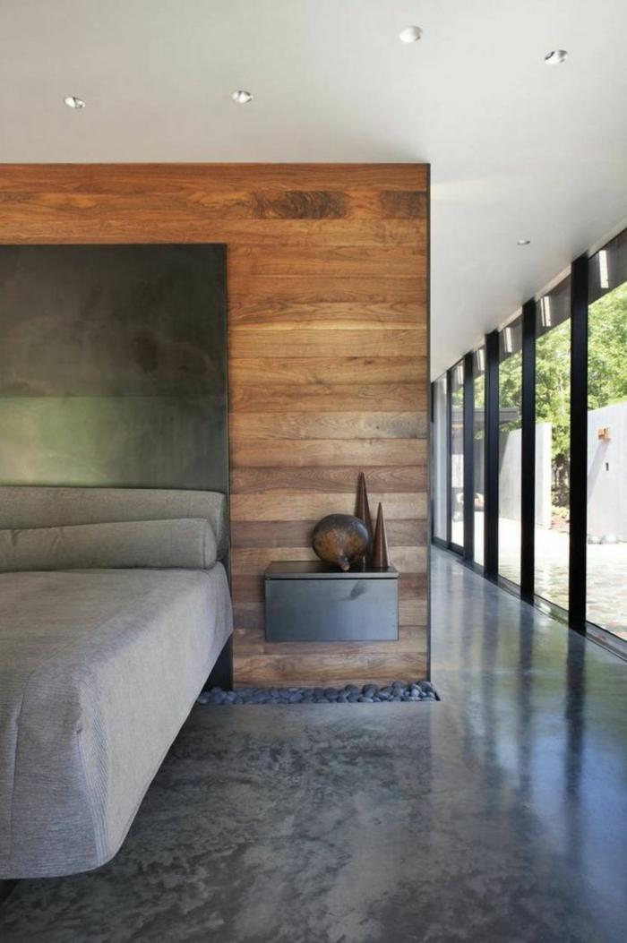 ein graues Bett, grauer Nachttisch, Betonboden Wohnbereich, Kies Dekoration, Betonboden Wohnbereich