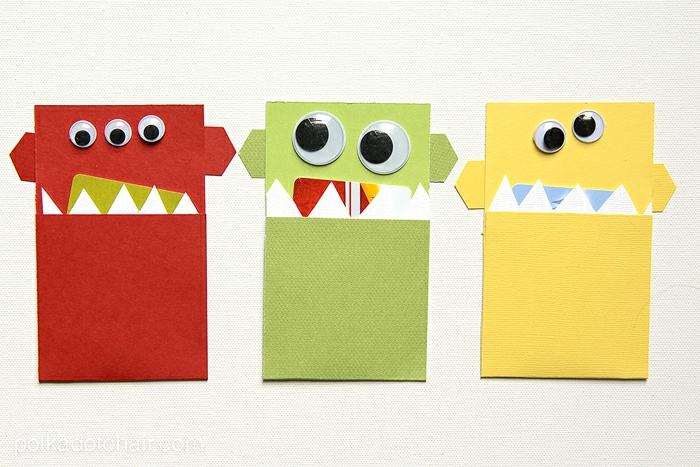 drei Ungeheuer mit Gutscheine im Mund, Gutschein verpacken zu Halloween, rotes Ungeheur mit drei Augen