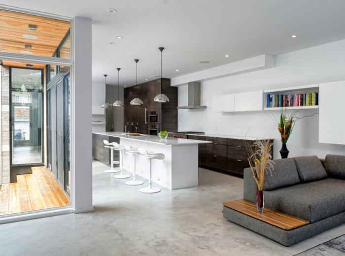 ein Einzimmerwohnung für die Ferien, Bar mit vier Hocker, ein graues Sofa, Betonboden Wohnbereich