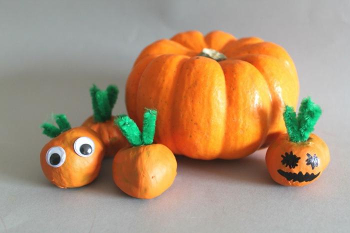 Herbst Bastelideen, vier kleinen Kürbisse aus Kastanien, ein echter kleiner Kürbiss, Augen auf den Kastanienkürbissen