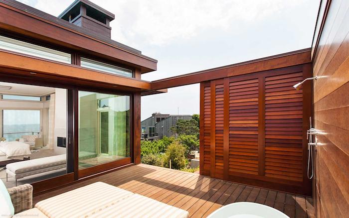 garten mit vielen grünen pflanzen und blättern, braunes haus aus holz, eine terrasse aus holz und mit sofas, ein wohnzimmer mit weißen sofas
