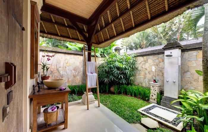 haus mit einem kleinen garten mit vielen grünen pflanzen und blättern, eine dusche und kleiner brauner tisch aus holz