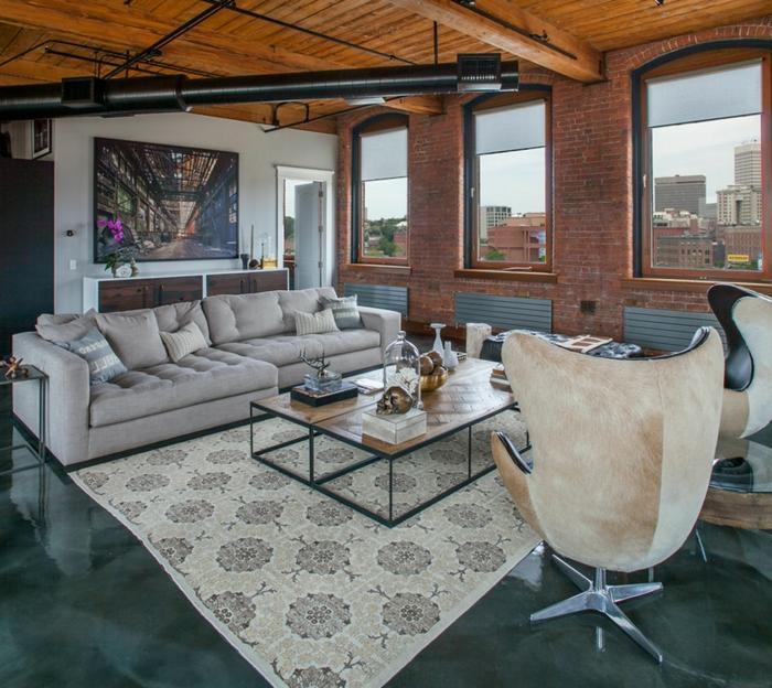 ein graues Sofa, zwei Sessel, ein Teppich mit Blumenmustern, Betonboden Wohnbereich