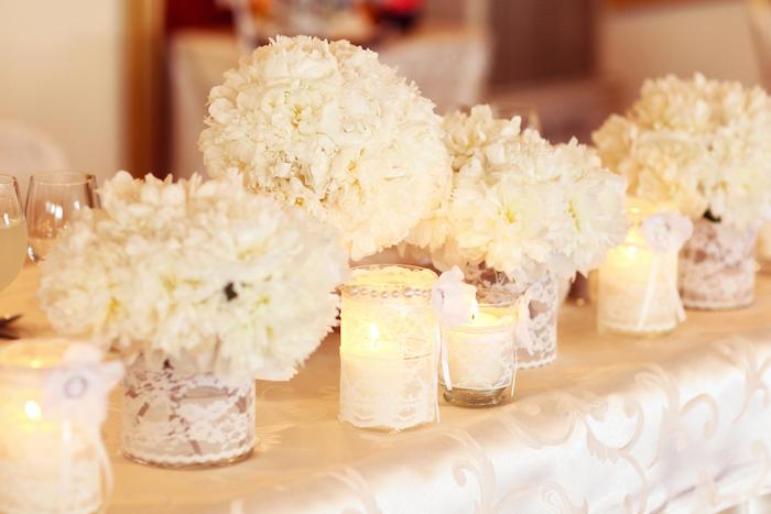 hochzeitsdeko tisch, tischdecke aus satin, weiße blumen, teelichter und vasen dekoriert mit spitzen