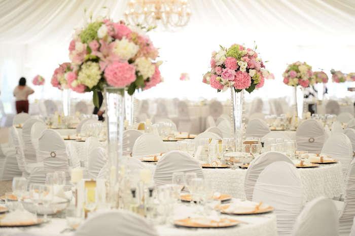 hochzeitsdeko tisch in weiß und rosa, große blumengestecke aus glas, goldene teller