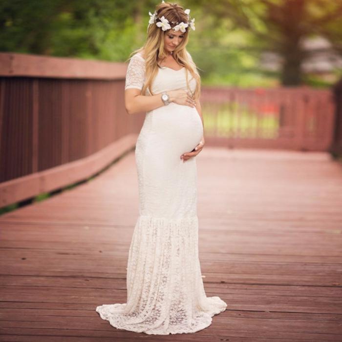 Umstandskleid Hochzeit, eine schöne schwangere Braut mit einem Blumenkranz, Spitzenkleid