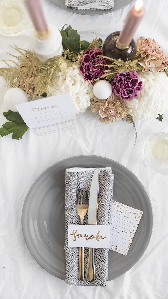 Simple Tischkarte, goldene Aufschrift auf weißem Zettel, Kerzenhalter dekoriert mit echten Nelken