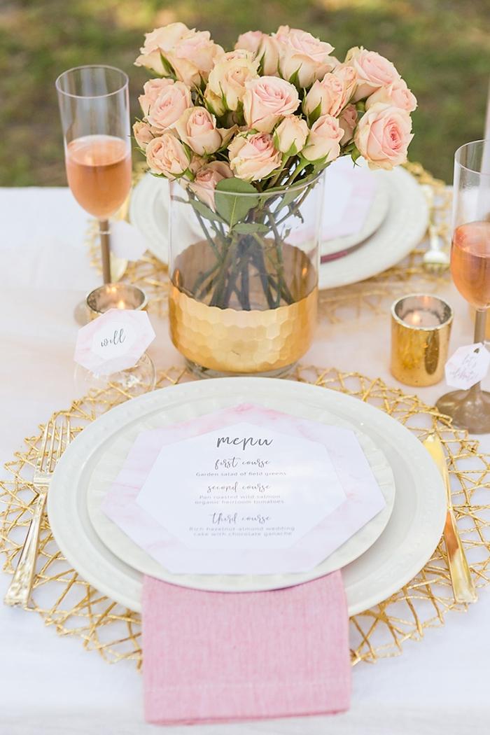 Platzkarte auf weißem Teller, schöner Rosenstrauß, kleine goldene Kerzenhalter