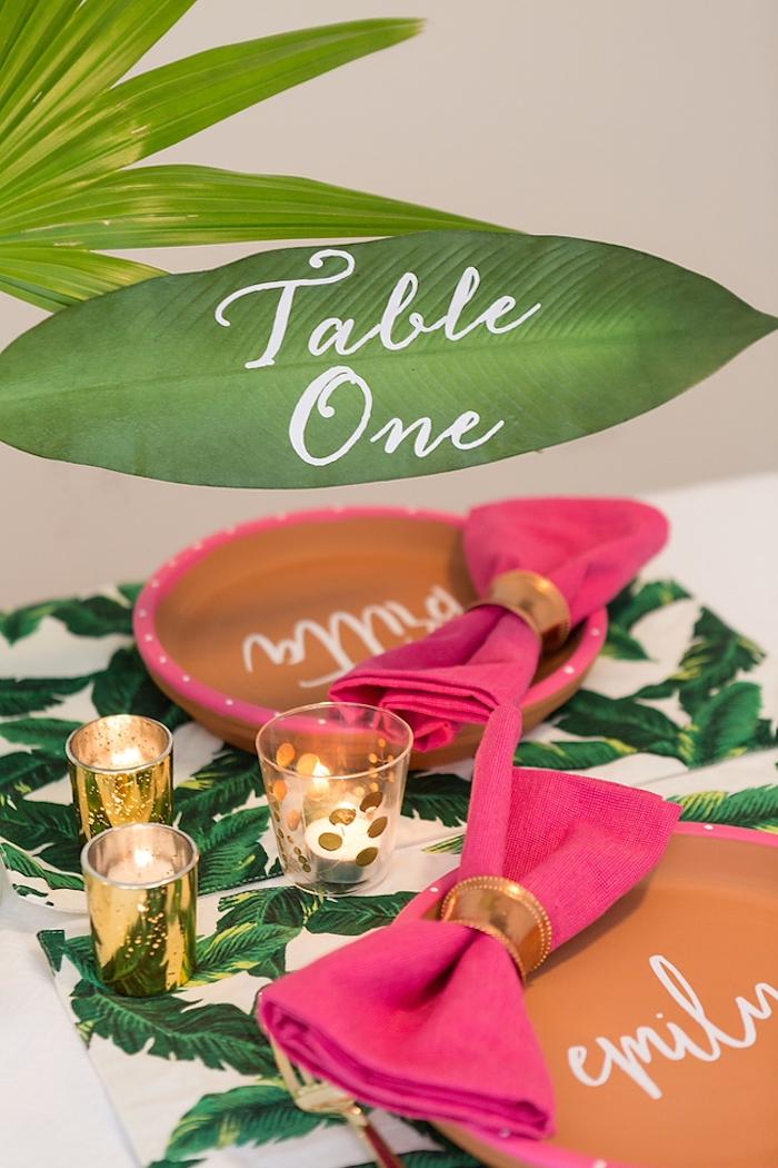 Tischnummer auf Blatt schreiben, violette Servietten und goldene Kerzenhlater