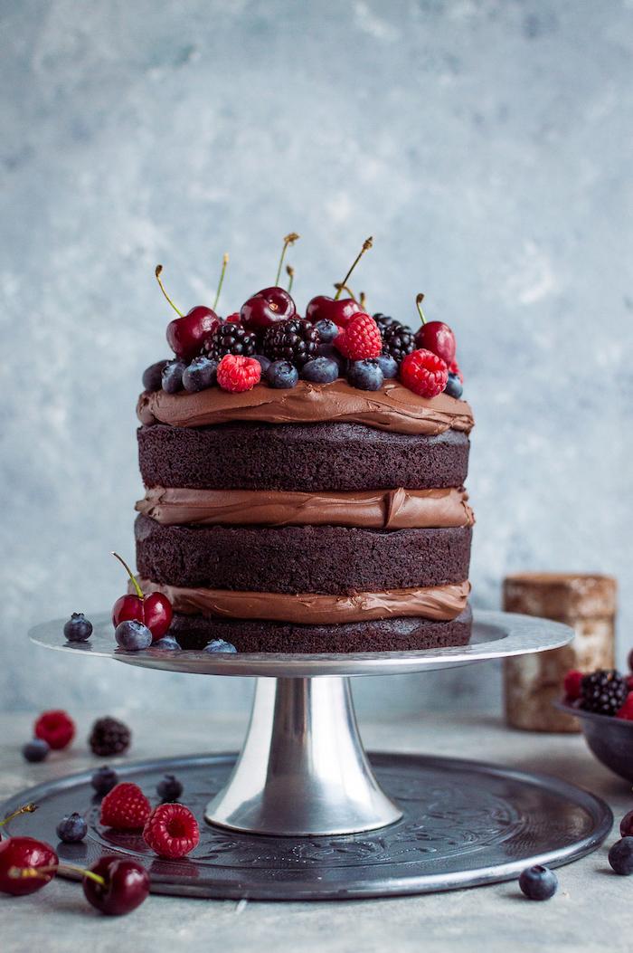 Dreistöckige Torte mit Schokoladencreme und frischen Früchten, drei Kakao Tortenböden