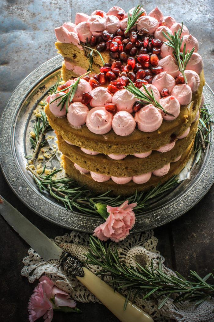 Dreistöckige Torte mit Erdbeercreme und Granatapfel, rosafarbene Nelken als Dekoration