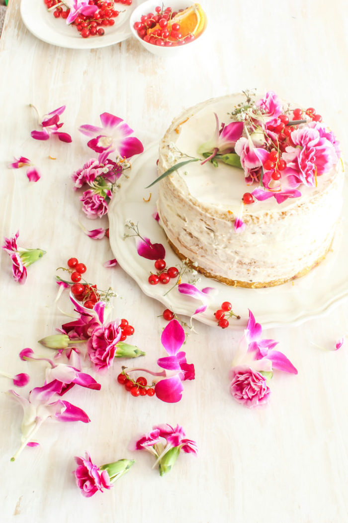 Selbstgemachte Torte mit Vanillecreme, dekoriert mit echten Blüten und Johannisbeere