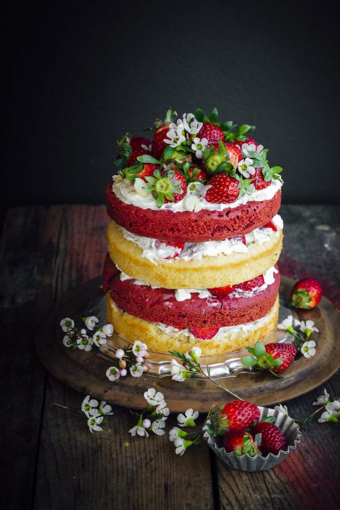 Dreistöckige Torte mit Vanillecreme und frischen Erdbeeren, dekoriert mit kleinen weißen Blüten