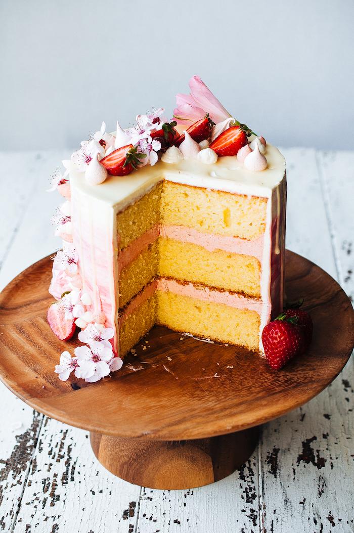 Dreistöckige Torte mit Erdbeercreme und weißer Schokolade, dekoriert mit kleinen Blüten und frischen Erdbeeren