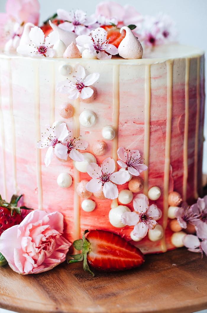 Dreistöckige Torte mit Erdbeercreme und weißer Schokolade, dekoriert mit echten Blüten und frischen Erdbeeren