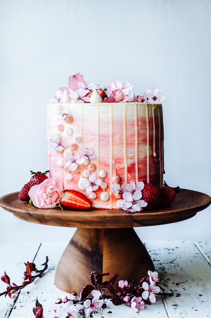 Prachtvolle selbstgemachte Hochzeitstorte mit weißer Schokolade, dekoriert mit echten Blüten und frischen Erdbeeren