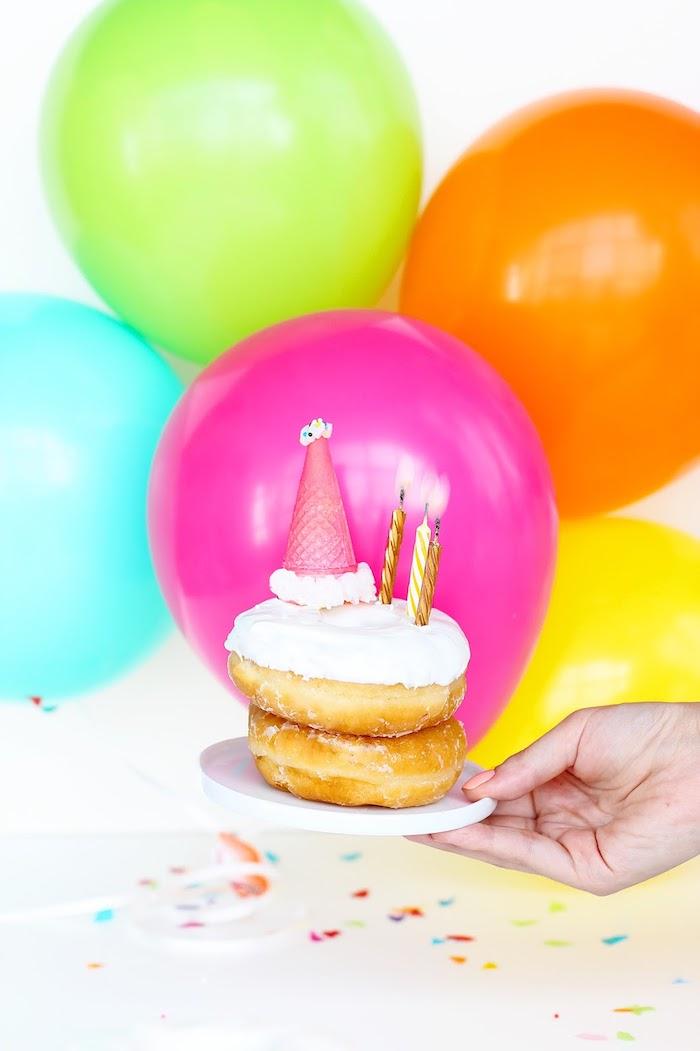 Leckere Donuts mit weißer Glasur und kleine Waffel, bunte Ballons im Hintergrund
