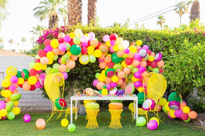 Gartenparty organisieren, Bogen aus bunten Ballons, Früchte aus Styropor auf dem Tisch