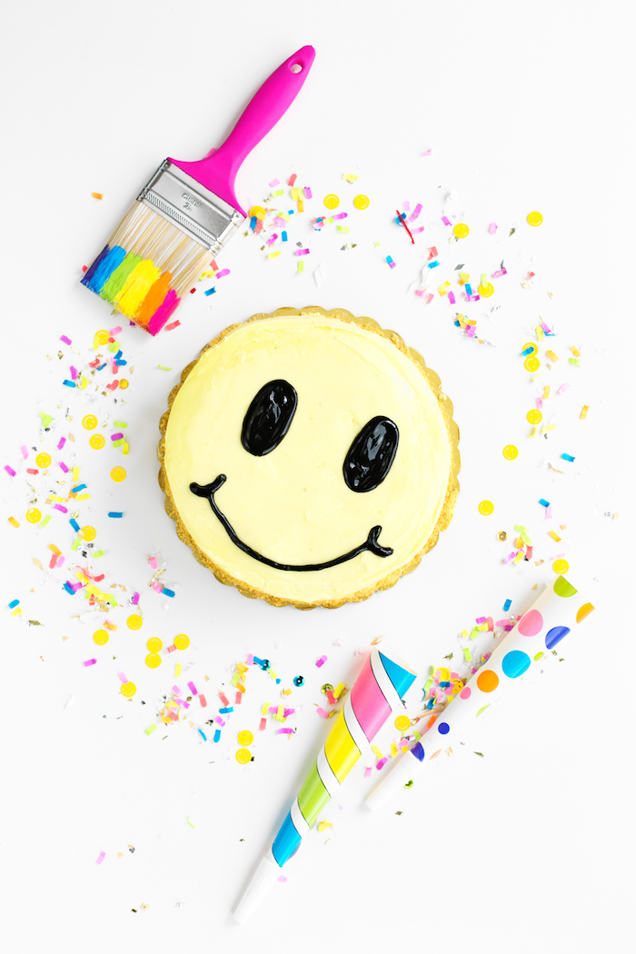 Smiley Torte selber backen und dekorieren, mit gelber Creme, Pinsel und Konfetti
