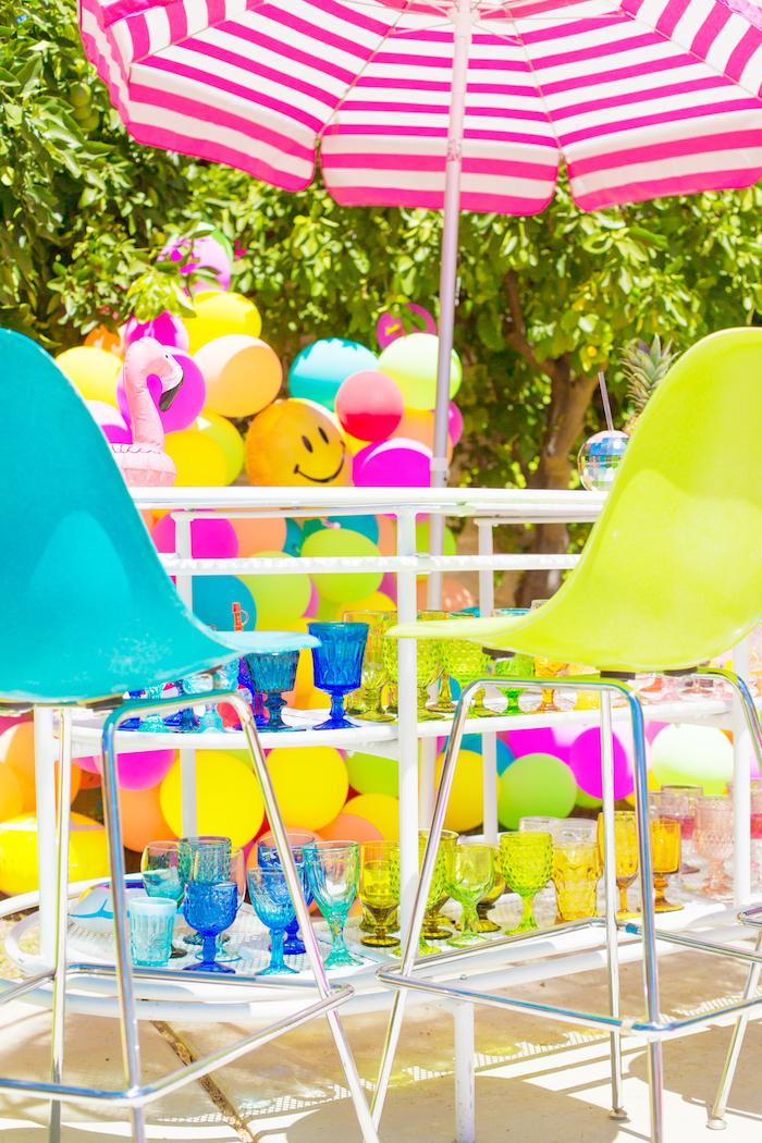 Poolparty zum Geburtstag organisieren, bunte Ballons und Gläser, gestreifter Sonnenschirm
