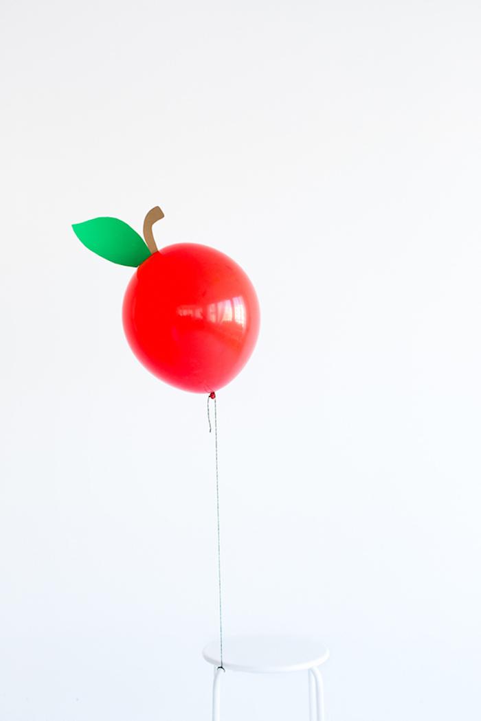 Roter Ballon als Apfel am Hocker befestigen, Blatt aus grünem Papier kleben