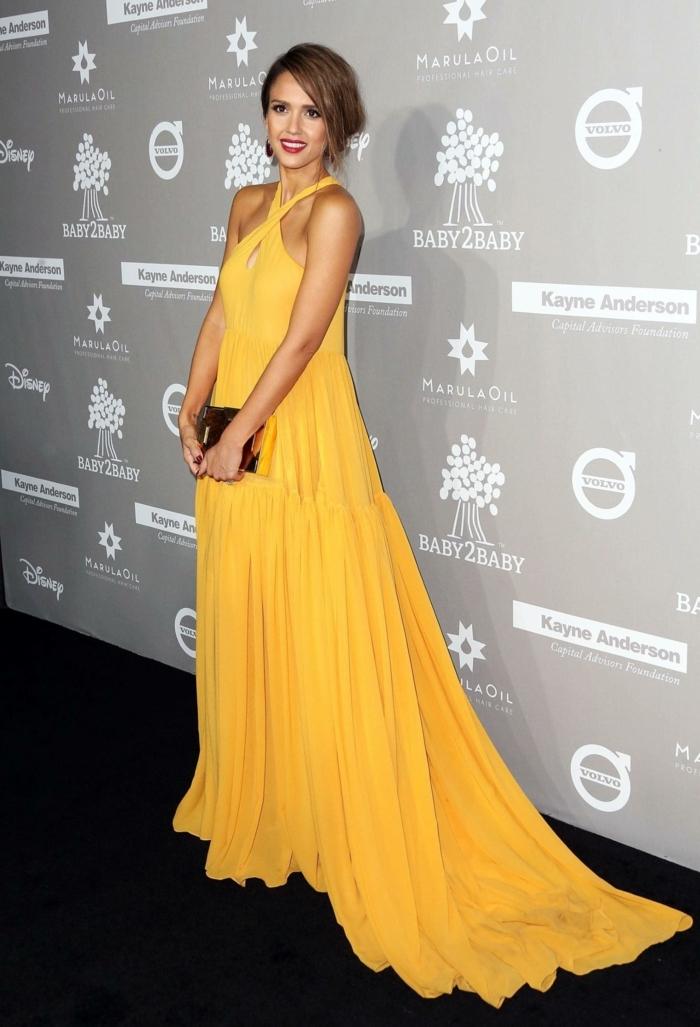 ein gelbes Kleid von Jessica Alba, kleine goldfarbene Tasche, dezentes Make up, Umstandskleider