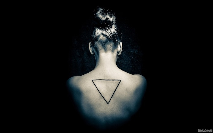 ein geometrisches tattoo mit einem großen schwarzen dreieck am rücken einer jungen frau, frauen tattoos ideen