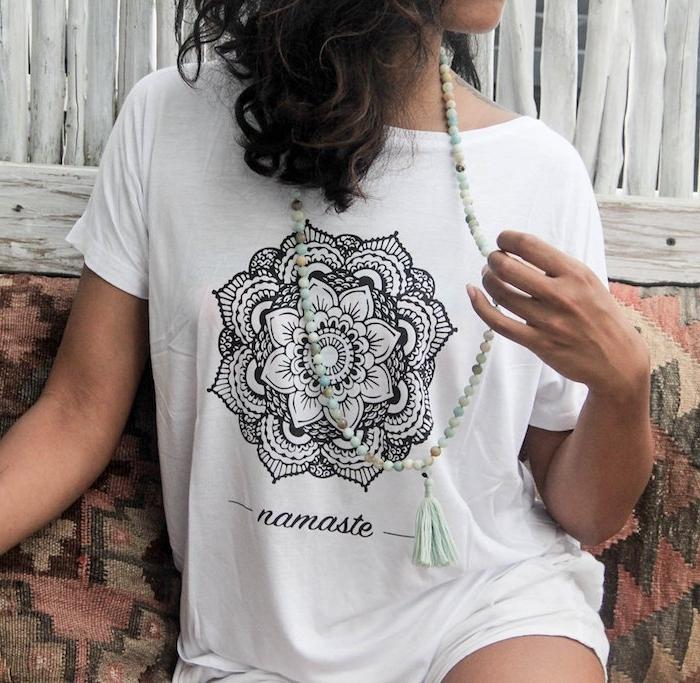 eine junge frau mit einem weißen t-shirt mit einem bild mit einer großen schwarzen mandala blume, frau mit einer großen grünen kette