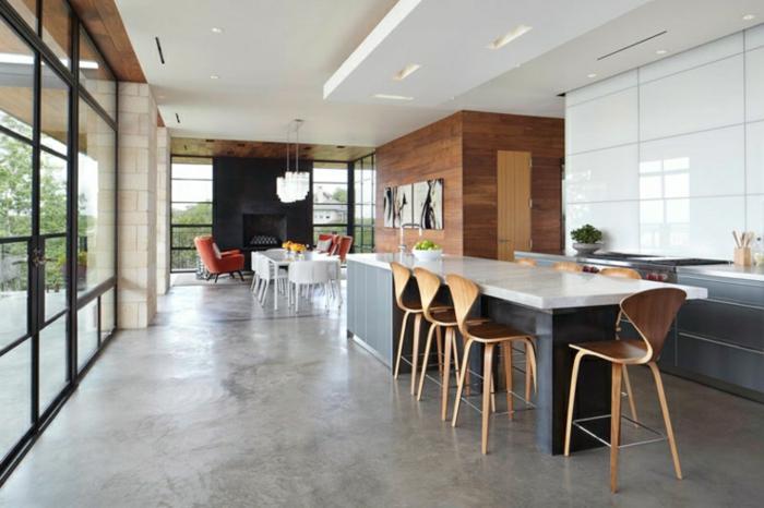 eine große Einzimmerwohnung, eine Theke mit hohen Hockern, Esszimmerbereich, Betonboden Wohnbereich