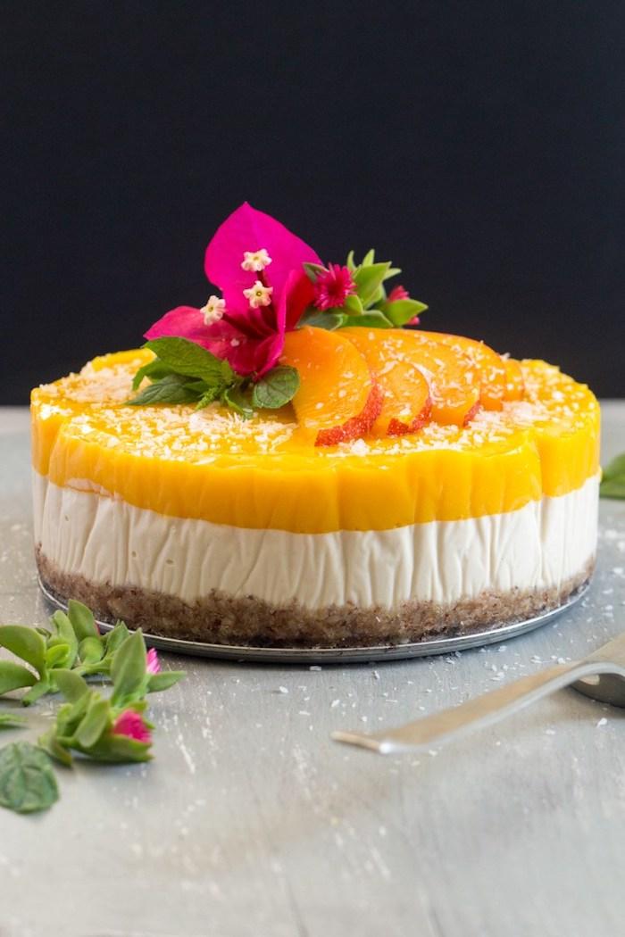 keksboden kuchen mit mango und ingwer, rosa blüten, stücke obst, frischkäsekuchen