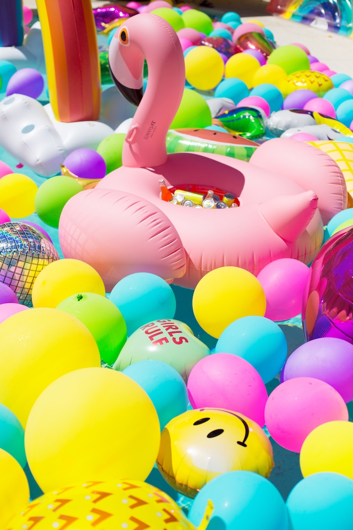 Aufblasbare Flamingo voll mit kühlen Getränken, viele bunte Ballons im Pool, die perfekte Poolparty planen