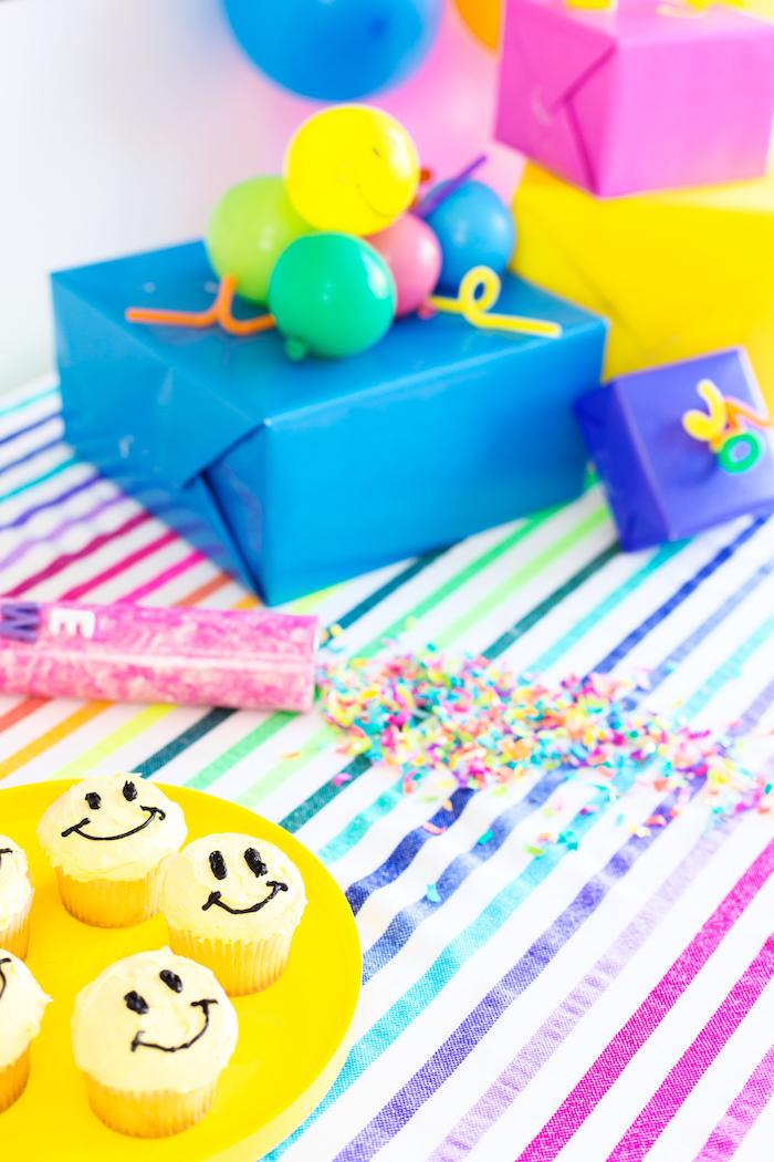 Smiley Cupcakes selber backen und dekorieren, mit gelber Creme, Geburtstagsgeschenke dekoriert mit kleinen Ballons