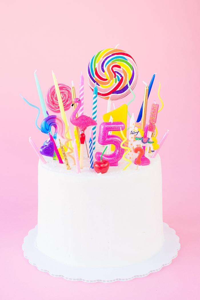 Geburtstagstorte mit weißer Glasur, verschiedene bunte Kerzen und Lutscher, Ideen für Kindergeburtstag
