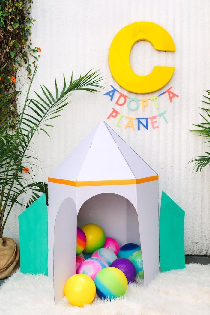 Lustige Spiele für Kindergeburtstag, Zelt aus Pappkarton in Form von Rakete, viele bunte Bälle darin
