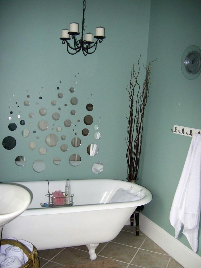 grüne Wände, kleine Spiegel mit gerundeter Form, eine weiße Wanne, trockene Blume in der Ecke