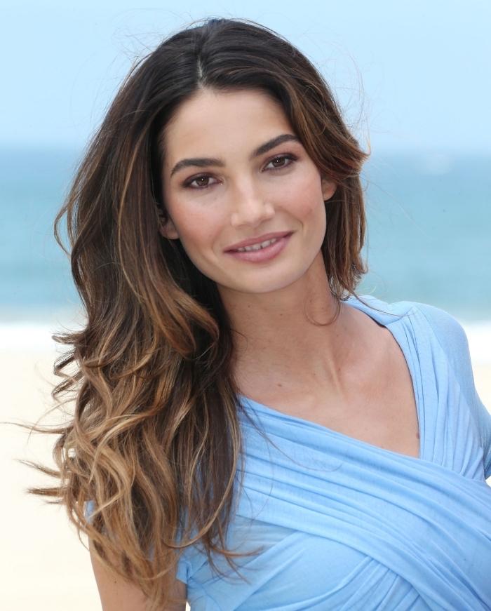Dunkelbraune Haare mit Babylights, langes welliges Haar mit Mittelscheitel, hellblaues Sommerkleid, leichtes Tages Make-up