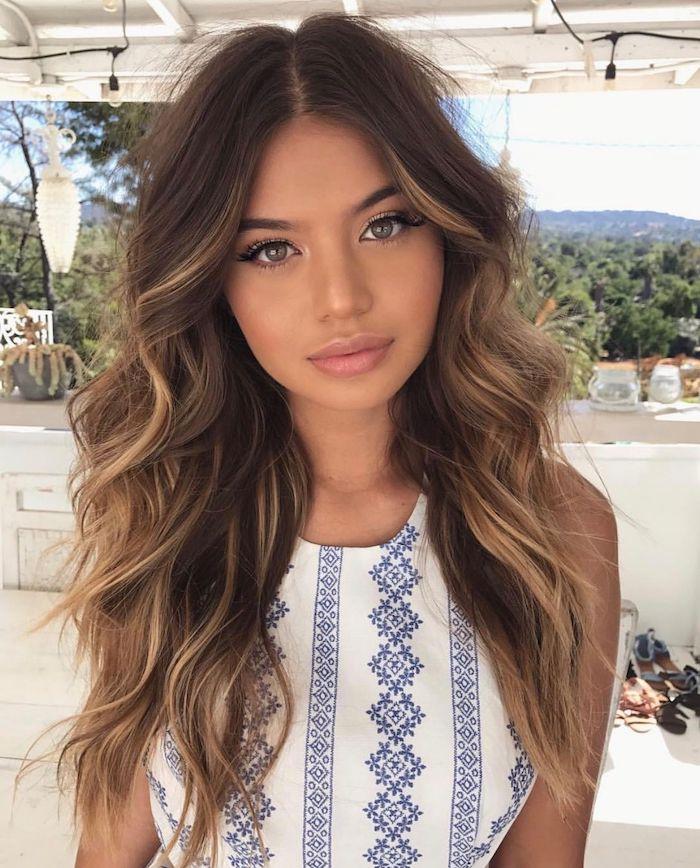 Lange und wellige Haare mit Mittelscheitel, blonde Strähnchen, gebräunter Teint und matter Lippenstift