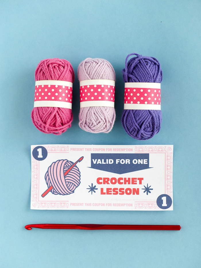ein Gutschein tum Häkeln Unterricht, eine Nadel und drei Stück Garn in rosa, grauer und blauer Farbe, Gutschein basteln