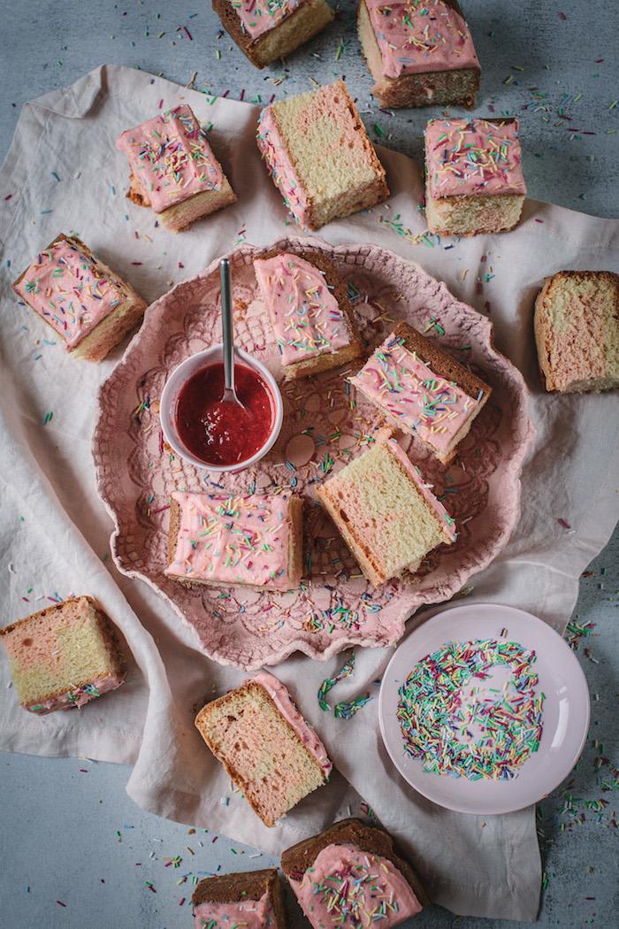 Leckere Torte mit Erdbeercreme und Zuckerstreuseln, Marmelade in kleiner weißer Schüssel