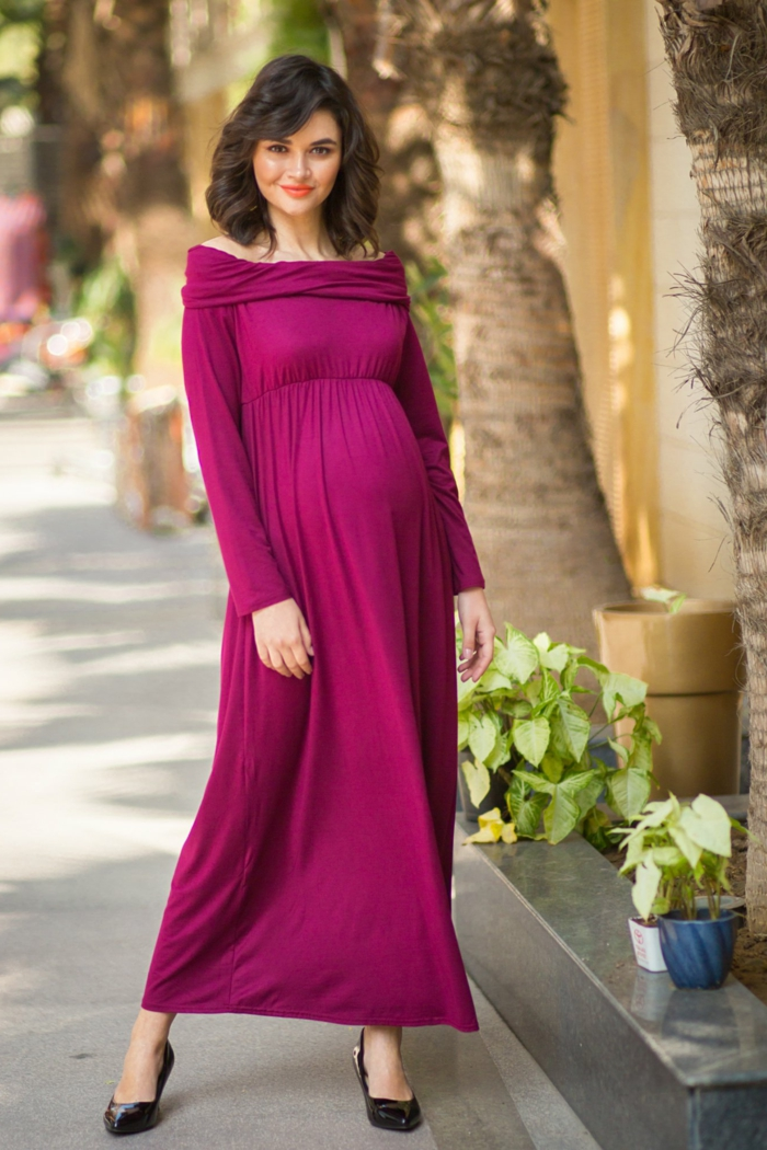 eine schöne werdende Mutter mit lila Kleid, Schwangerschaftskleid festlich mit schwarzen Schuhen kombiniert