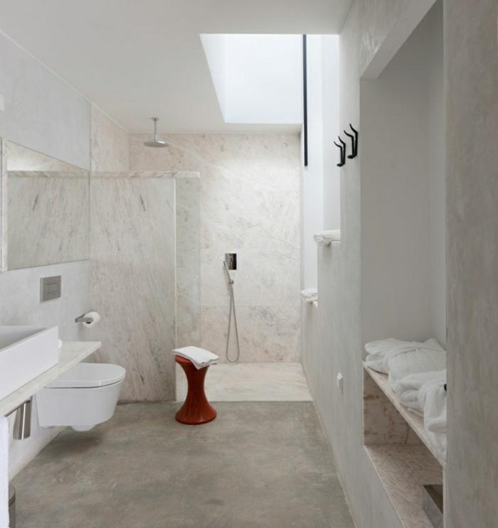 eine Duschkabine, kleiner Stuhl, Betonboden Wohnbereich, eine Bank an der Wand