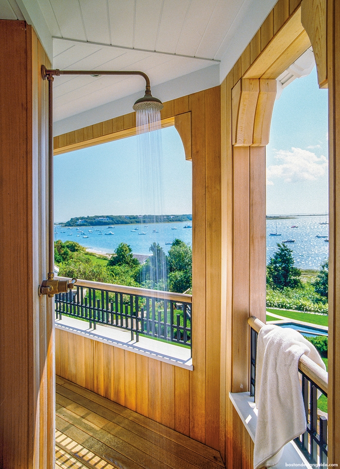haus mit einer terrasse aus holz und mit gartendusche, meer und garten mit rasen und grünen bäumen