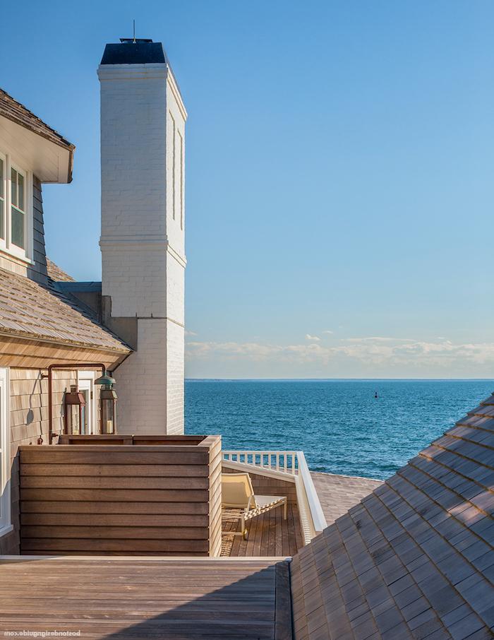 blauer himmel und ein haus mit terrasse aus holz und mit fenstern, meer und blauer himmel, terasse mit einer dusche