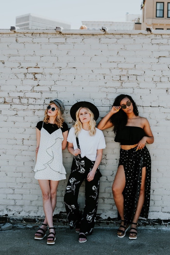 drei models, mittellange haare schnitt, schöne mädels an der wand fotos machen, blond, balayage und schwarze haare