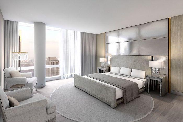 moderne schlafzimmer in weiß und grau, runder teppich, boden aus holz, lampen mit glasstielen