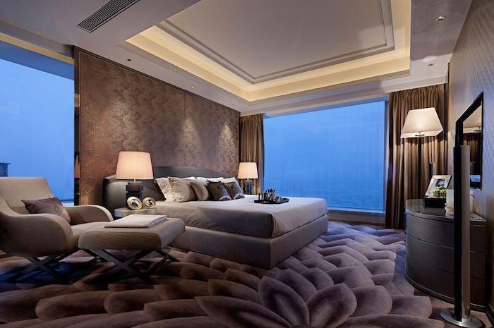 moderns chlafzimme,r groe fenster, teppich mit floramen motiv, designer lesesessel
