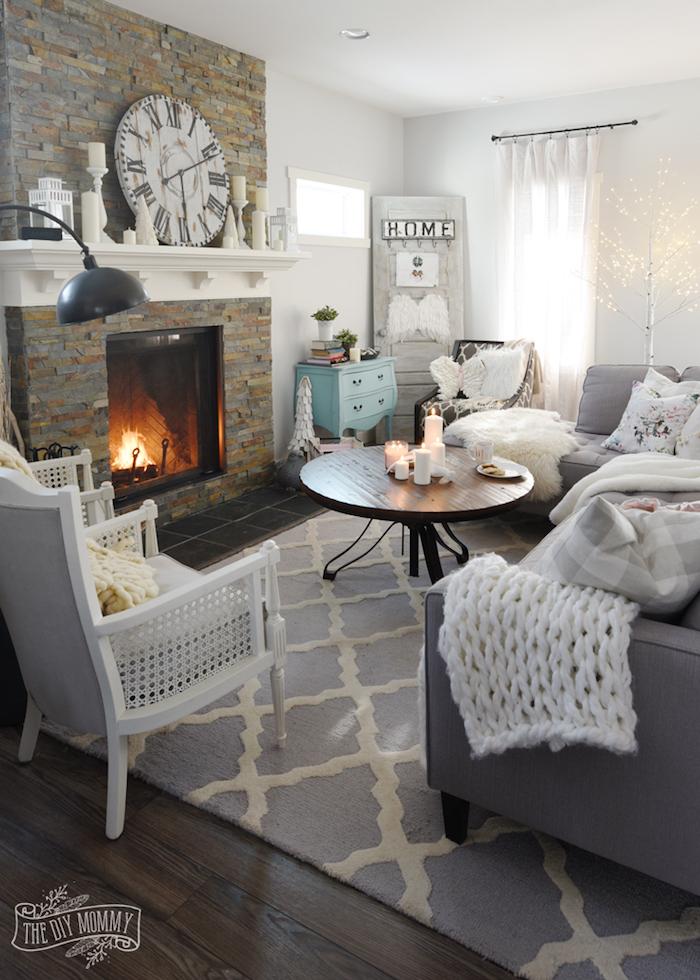 bild von einem wohnzimmer ideen zum nachmachen im skandinavischen design, weiße decken und deko, graue möbel, kamin, dezente einrichtung