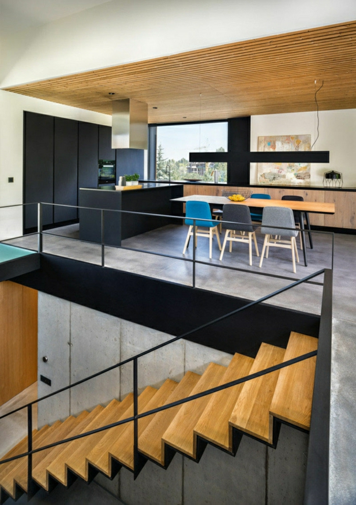 Treppe, Betonboden Wohnbereich, ein Esszimmertisch, eine schwarze Theke, ein schönes Bild