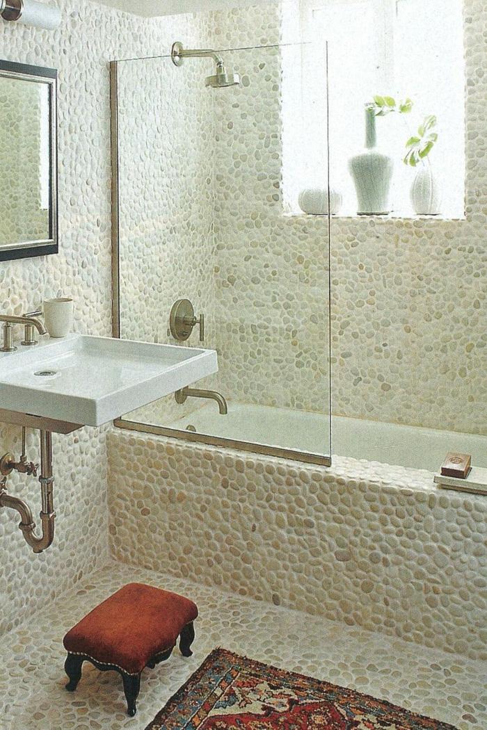 ein Badezimmer mit Narsteinoptik Mosaikfliesen, ein kleiner Waschbecken, ein Spiegel mit schwarzen Rahmen