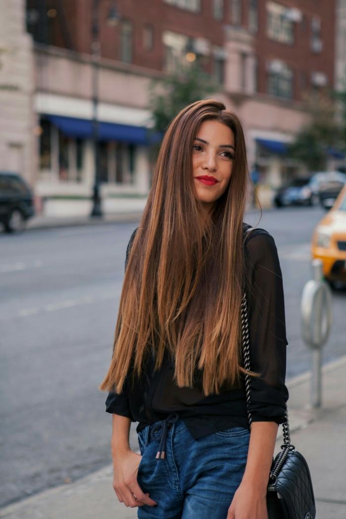 Lange und glatte braune Haare mit dunkelblonden Spitzen, schwarze Bluse und Jeans, roter Lippenstift